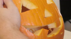 Man Inspects the Face of a Halloween Jack 'O' Lantern Stock Footage