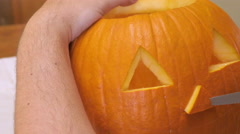 Man Carves a Nose in a Pumpkin to make a Jack 'o' Lantern Stock Footage