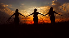 Silhouettes Against Red Sunset of Three Young Slender Girl Practicing Yoga Stock Footage