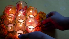 Hands decorating flowers and candles in a glass  during diwali celebration Stock Footage