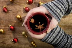 Cup of mulled wine in female hands with cinnamon stick, star anise and christmas Stock Photos