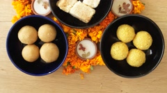 Tilt up close up across Indian sweets, flowers, diyas Stock Footage
