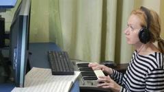 Woman writes music on the computer. digital piano midi keyboard Stock Footage