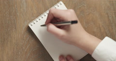 Female teen writes to do list on blank notepad Stock Footage
