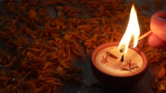 Man's hand lights up a traditional clay diya lamps marigold flowers Stock Footage