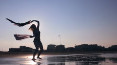 Girl silhouette dancing on beach with fabric fluttering on the wind against sun Stock Footage