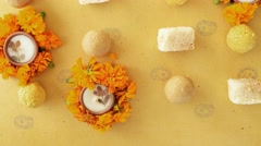 Tilt up Indian sweets, flowers, diyas on a Indian background Stock Footage