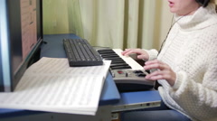 Woman writes music on the computer. digital piano midi keyboard Stock Footage