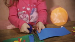 Cute little girl with scissors cuts paper in the glow of a Christmas garland Stock Footage