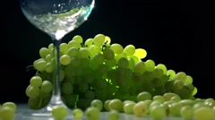 Pouring white wine into glass against the bunch of green grapes. Winemaking Stock Footage