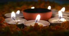 Hand lighting a Traditional clay diyas in between candles and flowers Stock Footage