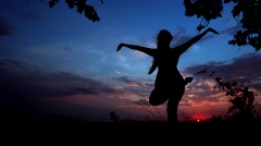 Silhouette Against Bright Color Sunset of One Young Graceful Girl Practicing Stock Footage