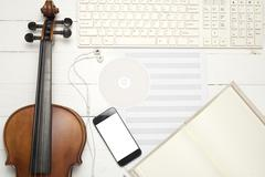 Violin with keyboard computer music paper note dvd disc and smart phone Kuvituskuvat