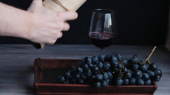 Pouring red wine into glass, Bunch (cluster) of purple red grapes on tray. Stock Footage