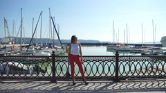 Young woman with long slender legs standing on the pier near the yacht club Stock Footage