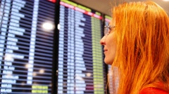 European young red hair woman looking at timetable departure board on airport Stock Footage