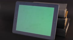 Tilt up to a green screen tablet touch screen resting on old books Stock Footage