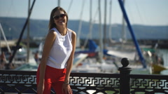 Woman at the pier near yacht on the background of blue sky, selective focus Stock Footage