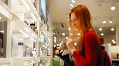 Young attractive woman with red hair choosing a perfume in duty free area at Stock Footage