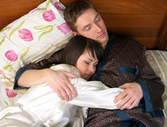 Young couple sleeping in the bed Stock Photos