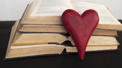 Tilt down and up from a red wooden heart on old books being taken away by a hand Stock Footage