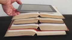 Tilt up Hands take away smart touch screen tab on open vintage books Stock Footage