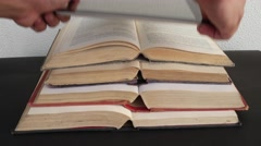 Hands place a smart touch screen tab on open vintage books Stock Footage