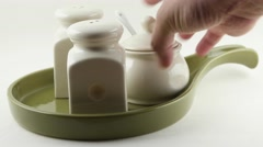 Closeup hand placing Ceramic salt and pepper dispenser and sugar bowl on a plate Stock Footage