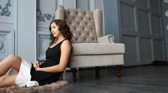 Beautiful woman in luxury interior sitting on the floor next to the armchair Stock Footage