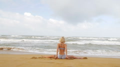 Young woman with a slender figure is engaged in stretching at sea Stock Footage