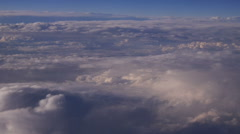 Mountain view from an airplane window above the earth in the blue sky in clouds Stock Footage
