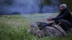 Man prepares camp fire Stock Footage