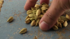 Close-up of hand sorting and selecting whole spices and seeds on wooden top Stock Footage