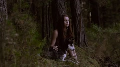Enigmatic young woman sitting in the forest with beautiful dog Stock Footage