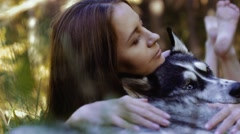 Close-up of attractive girl lying on grass hugging her husky dog Stock Footage