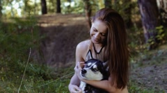 Pretty fair-skinned young woman sitting on knees and hugging dog is happy pan Stock Footage
