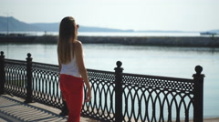 Beautiful young woman walking on pier Stock Footage