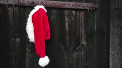 Santa hat hanging on old wooden door. Stock Footage