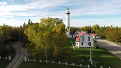 Fall colors Woods or Forest w Lake Lighthouse Aerial Flyover Liftoff   1 Stock Footage