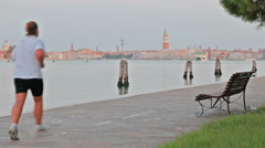 A group of people in white t-shorts doing morning sport run exersises in Venice Stock Footage