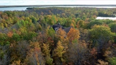 Fall colors Woods or Forest w Lake Aerial Liftoff house  1 Stock Footage
