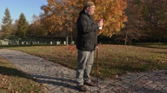 Disabled man with cane and coffee on path in cemetery Stock Footage