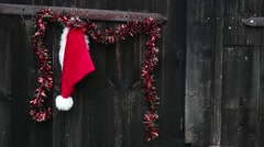 Santa hat and decorative chain hanging on old wooden door. Stock Footage