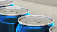 Carbonated soft drink or beer production line. Blue aluminum cans on industrial Stock Footage