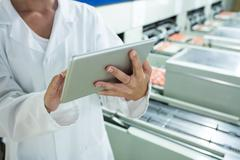 Mid section of female staff using digital tablet next to production line Stock Photos