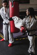 Man and woman practicing karate with punching bag Kuvituskuvat