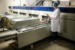 Female staff using digital tablet next to production line Stock Photos
