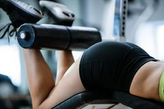 Woman performing exercise on bench press Stock Photos