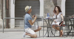 4K Couple with camera phone posing for photo at outdoor cafe table in the city Stock Footage