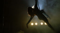Aerial acrobat woman on circus stage. Silhouette Stock Footage